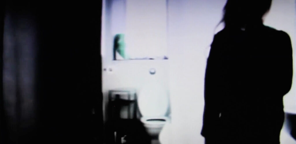 """A blurred image with a shadow of a young girl standing by a bathroom door, from Marko Lampisuo's short film """"4 Channel Edinburgh""""."""